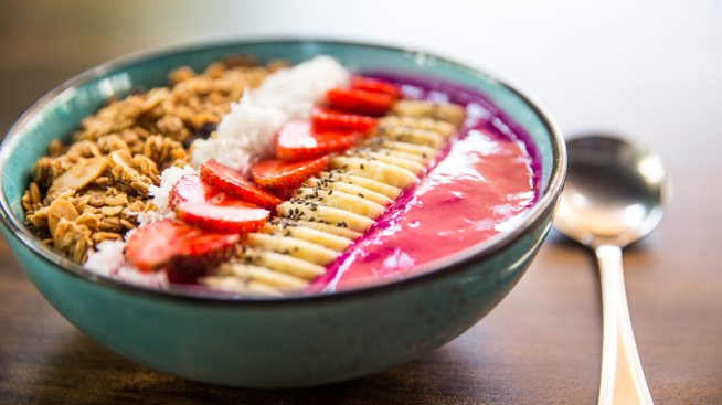 Dragon fruit smoothie bowl with strawberries, granola, chia seeds and banana.
