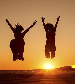 joyful women jumping up at the beach